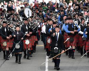 Andrew McLellan (centre) leads a mass parade of pipe bands  north along George St from the...