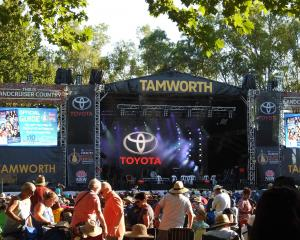 Visitors to Tamworth's Country Music Festival brave the heat, waiting for the opening concert to...