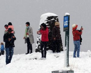 Falling snow and slush failed to stop tourists from taking photos at the Crown Range summit car...