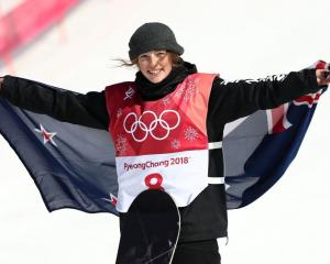 Zoi Sadowski Synnott holds the New Zealand flag after winning bronze at the Winter Olympics...