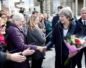 British Prime Minister Theresa May greets people after visiting the scene in Salisbury where...