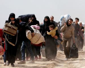 People walk with their belongings as they flee the rebel-held town of Hammouriyeh, in the village...
