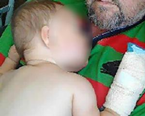 The injured baby with his grandfather shortly after the assault that left him hospitalised for a...