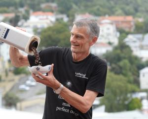 Chris Hilder pours beans from a coffee roaster into a bowl at a demonstration  featuring the new...