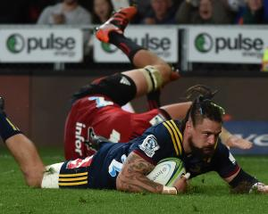 Highlanders loose forward Elliot Dixon scores a try during his team's Super Rugby match against...