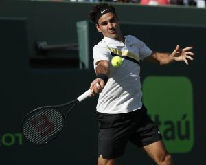 Roger Federer of Switzerland hits a forehand against Thanasi Kokkinakis of Australia. Photo: Reuters