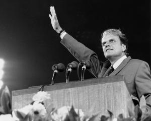 Evangelist Billy Graham preaches the Gospel to thousands of believers at Shea Stadium in Queens,...