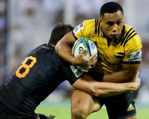 The Hurricanes' Ngani Laumape is caught by the Jaguares' Tomas Lezana. Photo: Getty
