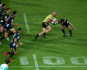 TJ Perenara breaks the Highlanders defence during his 100th game in the round six Super Rugby...