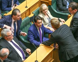 Simon Bridges talking with other National MPs in Parliament. Photo: Getty Images