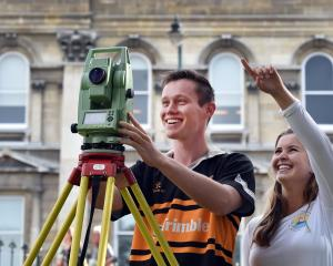Fourth-year surveying students Jackson Clark (21) and Jess Smyth (21) with a ``total station'',...