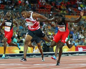 Zharnel Hughes (left) and Jereem Richards cross the finish line of the 200m final at the...