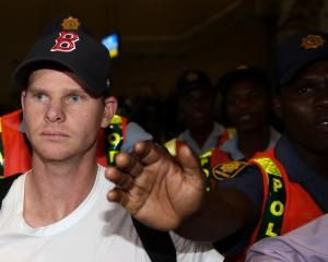 Former Australian cricket captain Steve Smith is escorted by police officers while leaving South...