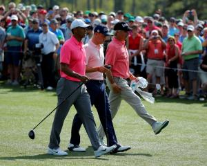 US golfers Tiger Woods (L), Justin Thomas (C) and Fred Couples walk up the 8th fairway during...