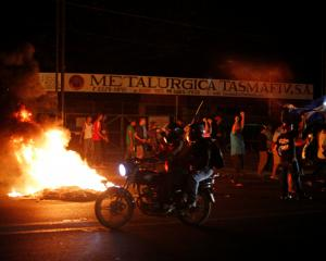 Demonstrators shout next to a burning barricade as they take part in protests in Managua,...
