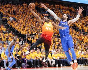 Utah Jazz guard Donovan Mitchell (45) tries to keep Oklahoma City Thunder center Steven Adams (12...