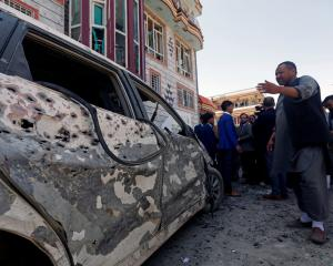 Afghan men inspect the site of a suicide bomb blast in Kabul, Afghanistan. Photo: Reuters