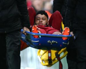 Liverpool's Alex Oxlade-Chamberlain is stretchered off the field in yesterday's Champions League...