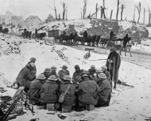 A scene on the British Western Front: troops warming themselves around a fire by the roadside. —...