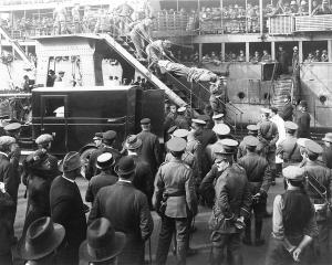 A solemn crowd watches in silence as the first wounded from Gallipoli disembark from TS Willochra...