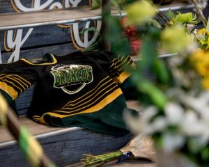A Humboldt Broncos team jersey is seen among notes and flowers at a memorial for the Humboldt...