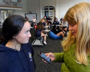 Otago Girls' High School pupil Oceana Campbell (14, left) answers questions on a concussion app...