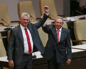 Newly elected Cuban President Miguel Diaz-Canel (L) reacts as former Cuban President Raul Castro...