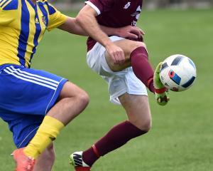 University defender Tom Ford (left) and Dunedin Technical striker Tim McLennan compete for the...