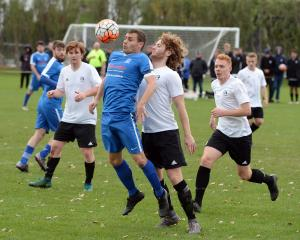 Mosgiel's Cameron McPhail prepares to head the ball while  surrounded by Roslyn-Wakari players ...