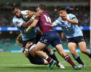 Waratahs winger Taqele Naiyaravoro carries Reds players with him as he crosses to score. Photo:...