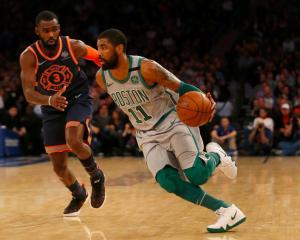 Boston Celtics guard Kyrie Irving (with ball) drives past New York Knicks' guard Tim Hardaway Jr...