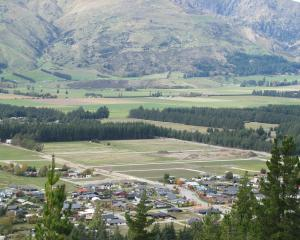 Lake Hawea township - showing bare land in the top half of the photograph beyond pine trees,...