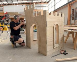 GJ Gardner carpentry apprentice Jeff Bell builds a children's castle playhouse as part of the...