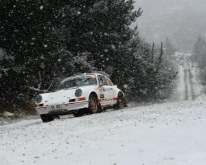 Allan Dippie, of Dunedin, powers his Porsche 911 into a corner as snow falls in Flagstaff...
