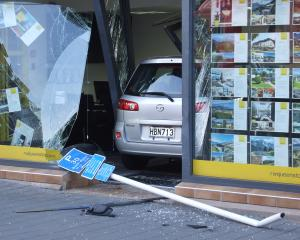 The car crashed through the front window of Ray White's Church St premises this morning. Photo...