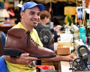 Former refugee Mohamad Ghanam holds a giant shoe at his workplace, McKinlay's Footwear. Photo:...