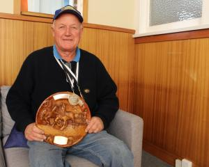 Alistair Rutherford, of Waimumu, displays his two new gold medals and trophy from the New Zealand...