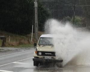 A motorist takes on surface flooding on Aubrey Rd in Wanaka today. Photo: Sean Nugent