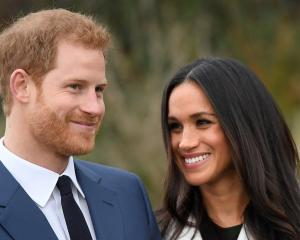 Prince Harry poses with Meghan Markle in the Sunken Garden at Kensington Palace in London. Photo...