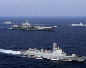 Chinese aircraft carrier Liaoning (C) takes part in a military drill in the western Pacific Ocean...