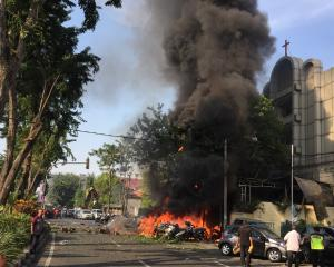 Motorcycles burn following a blast at the Pentecost Church Central Surabaya. Photo: Reuters