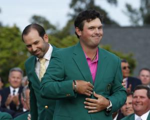 Sergio Garcia of Spain (rear) looks on after helping put the green jacket on 2018 Masters winner...