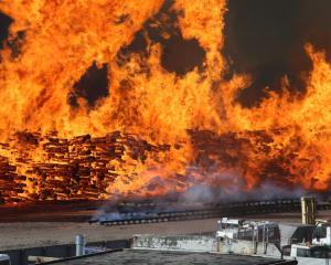 The Burnside fire burns through Valley Lumberyard on McLeod's Rd in January. Photo: Chris &...