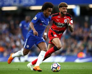 Willian of Chelsea is challenged by Philip Billing of Huddersfield Town this morning. Photo:...