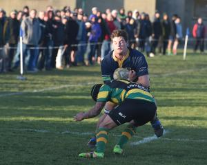 Dunedin No8 Jamie Mowat tries to bump off the tackle of Green Island midfield back Sam Eriepa at...