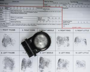 Fingerprints with loupe on arrest form in forensic laboratory. Photo: Getty Images