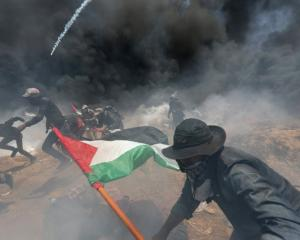 Palestinian demonstrators run for cover from Israeli fire and tear gas during a protest against...