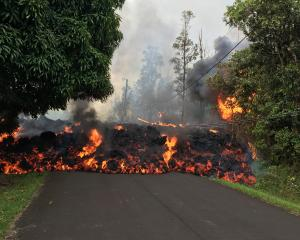 Lava flows from the crater of Kilauea volcano as dozens of structures, including at least nine...