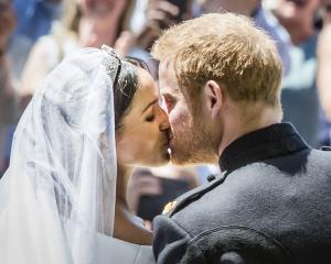 Prince Harry, Duke of Sussex, and Meghan Markle, Duchess of Sussex, kiss on the steps of St...