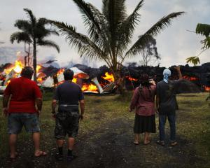 Community members watch as a home is destroyed by lava from a Kilauea volcano fissure in Leilani...